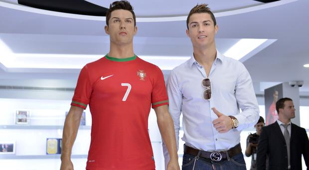 Cristiano Ronaldo poses next to a model of himself wearing the Portuguese national team kit during a tour of his museum in Funchal, Portugal