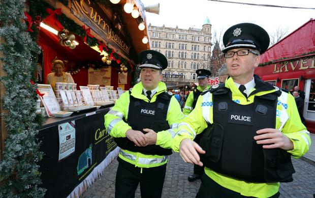 Chief Constable Matt Baggott (left) and Assistant Chief Constable Will Kerr visit the Christmas market in front of the City Hall where they met traders in the wake of last weeks bomb attack in the city