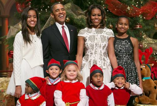 US President Barack Obama (2nd L), his wife Michelle (2nd R) and their daughters Malia (L) and Sasha (R) are greeted by a team of elves made up of former patients of the Children's National Medical Centre. Photo: Reuters