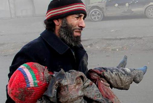 A Syrian man cries while holding the body of child who was killed following a Syrian government airstrike in Aleppo.