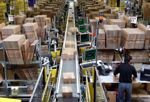 Workers pack boxes at Amazon's logistics centre in Graben near Augsburg December 16, 2013. Workers at Amazon.com's German operations were set to go on strike on Monday, in the middle of the crucial Christmas holiday season, in a dispute over pay that has been raging for months