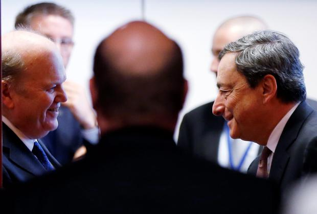 Finance Minister Michael Noonan talks to European Central Bank (ECB) President Mario Draghi (R) during an eurozone finance ministers meeting in Brussels