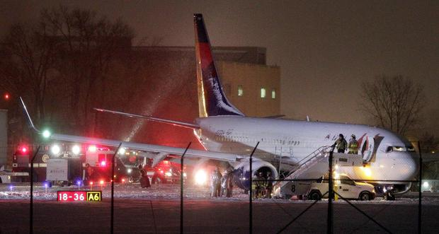 Authorities investigate the scene of a Delta Air Lines Boeing 737-800 jet that slid off a runway in the snow after arriving at Dane County Regional Airport in Madison, Wisconsin. No one was hurt. (AP Photo/Wisconsin State Journal, M.P. King)
