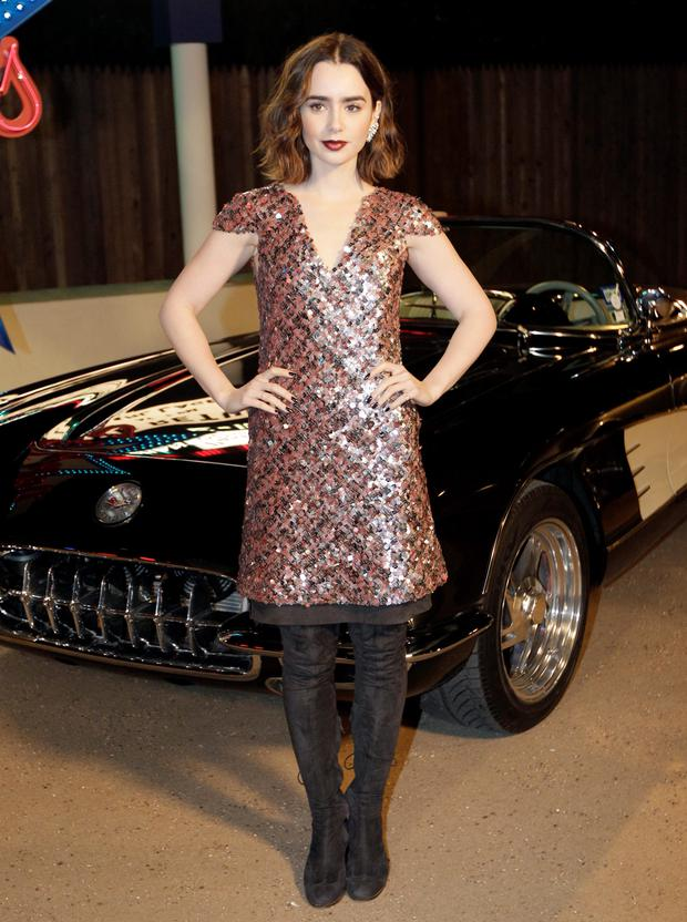 Actress Lily Collins poses for photos after arriving for Chanel's Metiers d'Art fashion show in Dallas. (AP Photo/Tony Gutierrez)