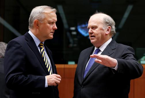 European Union Economic and Monetary Affairs Commissioner Olli Rehn listens to Ireland's Finance Minister Michael Noonan (R) during a eurozone finance ministers meeting in Brussels