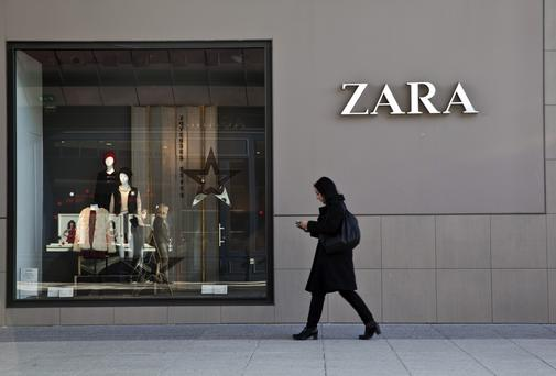 A pedestrian passes the window display of a Zara fashion store
