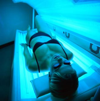 Woman lying in a tanning machine