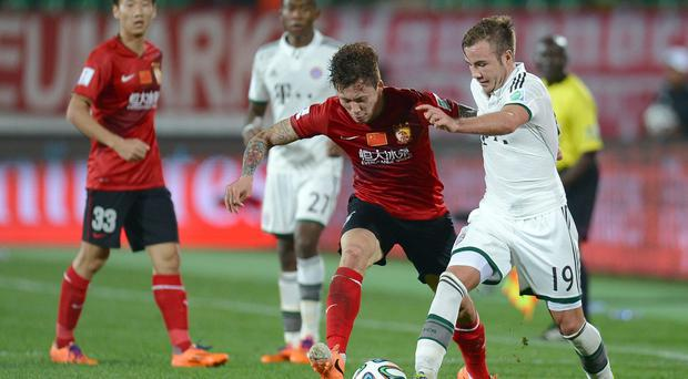 Linpeng Zhang of Guangzhou challenges Mario Goetze of Muenchen during the FIFA Cub World Cup semifinal match between Guangzhou Evergrande and Bayern Muenchen at Agadir Stadium on December 17, 2013 in Agadir, Morocco