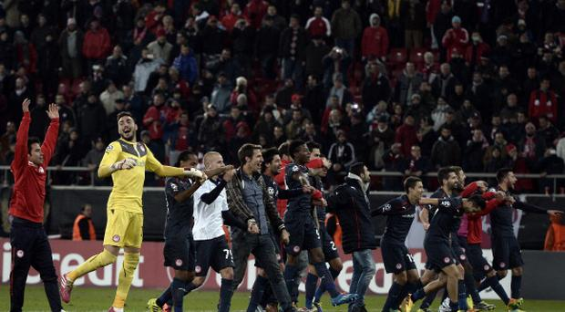 Olympiakos' players celebrate after winning their UEFA Champions League group C football match against Anderlecht at the Karaiskaki stadium in Athens on December 10, 2013 ARIS MESSINIS/AFP/Getty Images)
