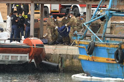 Italian military personnel disembark from a boat carrying the bodies of African migrants killed in a shipwreck off the Italian coast lie in Lampedusa harbour in October.