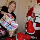 Princess Charlene of Monaco (L) distributes gifts to Monaco's children beside a Santa Claus during the traditional Christmas tree ceremony at the Monaco Palace.