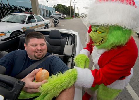 Major Lou Caputo, of the Monroe County Sheriff's Office, dressed in costume as the Grinch, in Marathon, Fla. Fedigan gives motorists who travel about 5 mph or less above the school zone speed limit the option of a traffic citation or an onion