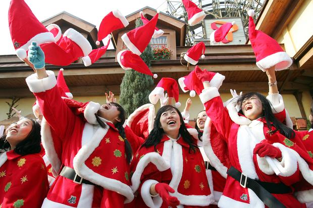 YONGIN-SI, SOUTH KOREA - NOVEMBER 26: South Koreans dressed in Santa Claus costumes throw their hats in the air in celebration after a graduation ceremony at a Santa Claus School class for the Christmas holiday season at the Everland amusement park on November 26, 2008 in Yongin, South Korea. Christmas has become increasingly popular over the years in South Korea, which is the only East Asian country to recognize Christmas as a national holiday. (Photo by Chung Sung-Jun/Getty Images)