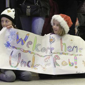Katie and Ciara O' Toole from Lusk wait on uncle Rob O'Toole who lives in Alberta Canada at Dublin Airport.