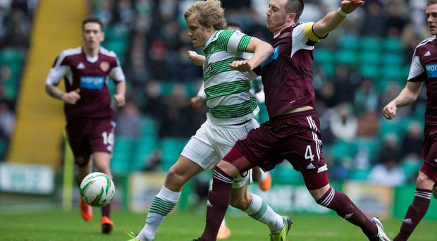 Celtic's Teemu Pukki (left) and Hearts Danny Wilson (right) battle for the ball during the Scottish Premiership match at Celtic Park, Glasgow. PRESS ASSOCIATION Photo. Picture date: Saturday December 21, 2013. Jeff Holmes/PA Wire.