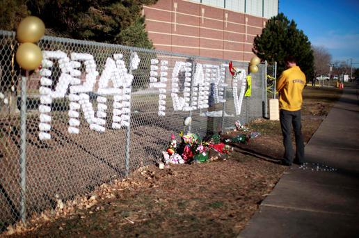 An Arapahoe high school student prays at the school in Centennial, Colorado December 15, 2013. Claire Davis, a 17-year-old Colorado high school senior shot in the head December 13 by a heavily-armed classmate who stormed the school died today