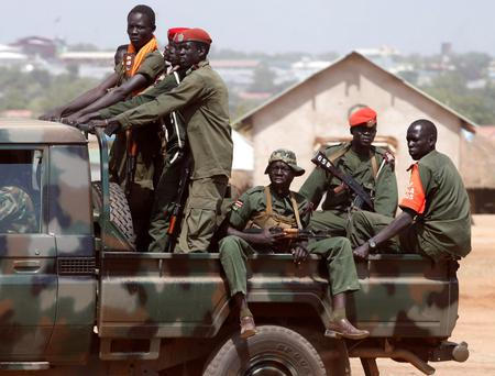 SPLA soldiers drive in a vehicle in Juba December 21, 2013. African mediators sought on Saturday to meet rivals to South Sudan's president in a bid to end fighting that threatens to drag the world's newest country into an ethnic civil war