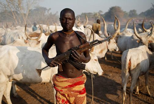 A man from Dinka tribe holds his AK 47 rifle in front of cows in a Dinka cattle herders camp near Rumbek, capital of the Lakes State in central South Sudan December 14, 2013. Picture taken December 14, 2013. REUTERS/Goran Tomasevic (SOUTH SUDAN - Tags: SOCIETY ANIMALS TPX IMAGES OF THE DAY)
