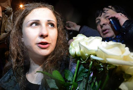 Maria Alyokhina, one of the jailed members of anti-Kremlin punk band Pussy Riot, is surrounded by journalists and her supporters as she arrives in Moscow on December 23, 2013
