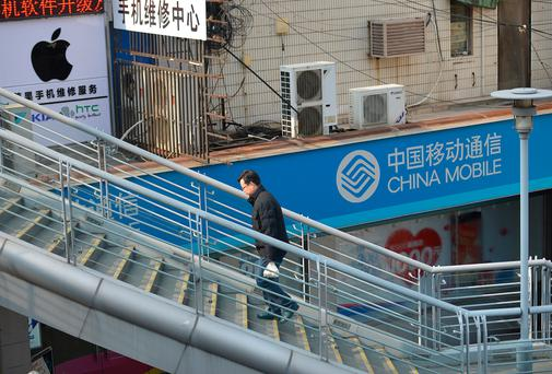 A man walks past a China Mobile sign and an Apple sign on a street in Shanghai