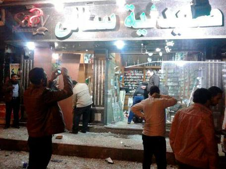 People walk around a damaged shop after an explosion at a security building in Mansoura city, the capital of Dakahlyia Governorate