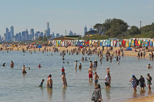 People enjoy a day at the beach on Christmas Day at Brighton Beach on December 25, 2013 in Melbourne, Australia.