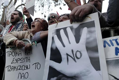 Protesters chant slogans outside the Cypriot parliament in Nicosia in March
