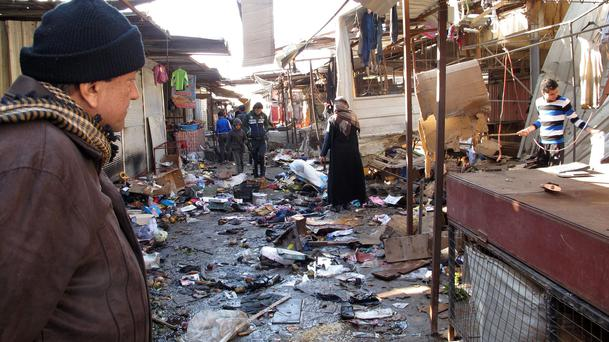 A man looks at the site of bomb attack at a marketplace in Baghdad's Doura District December 25 2013.