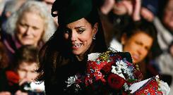 Kate Middleton collects flowers from well-wishers as she leaves a Christmas Day service at the church on the Sandringham Estate in Norfolk.