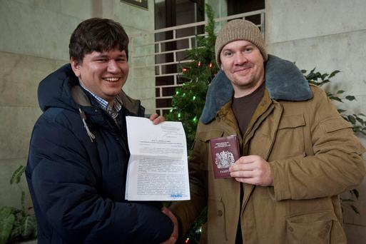 Greenpeace International activist Anthony Perrett (R) from Britain poses with his lawyer Sergey Golubok, who holds papers certifying the termination of prosecution, after he became the first of the 30 Greenpeace Arctic activists to have the criminal case against him dropped, in Saint Petersburg, December 24, 2013, in this handout image courtesy of Greenpeace. Russia formally dropped criminal charges against the Greenpeace activists arrested in a protest over Arctic oil drilling on Wednesday, under a Kremlin amnesty extended to all 30 who had been facing up to seven years jail if convicted. Picture taken December 24. REUTERS/Dmitri Sharomov/Greenpeace/Handout via Reuters