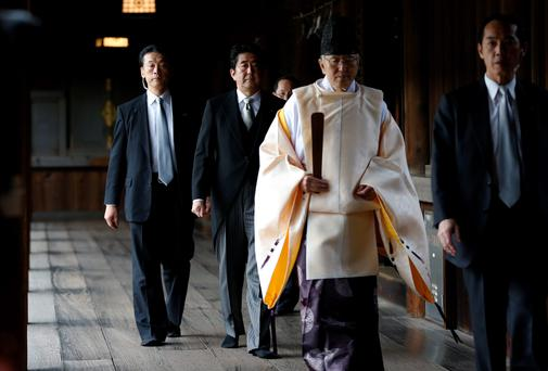 Japan's Shinzo Abe walks behind a Shinto priest. Mr Abe is the first Japanese prime minister to visit Yasukuni shrine, which honours Japan's war dead, in seven years. TORU HANAI/ REUTERS