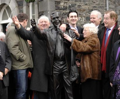 Paddy Dolan is pictured to the left of the statue which was erected in Mullingar to honour his famous singer brother Joe.