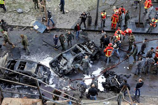 Civilians, soldiers and policemen gather at the site of an explosion in downtown Beirut