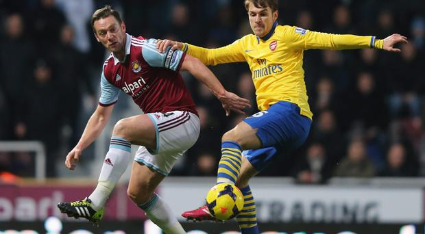 Aaron Ramsey of Arsenal (right) holds off Kevin Nolan of West Ham United