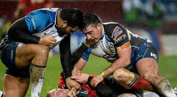 Keith Earls, Munster, is held on the ground off the ball by Rodney Ah You, left, and Denis Buckley,