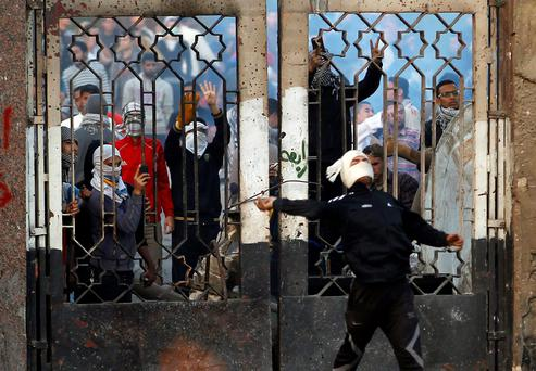 A student of Al-Azhar University, who is a supporter of the Muslim Brotherhood and deposed President Mohamed Mursi, throws stones as another takes pictures during clashes with riot police