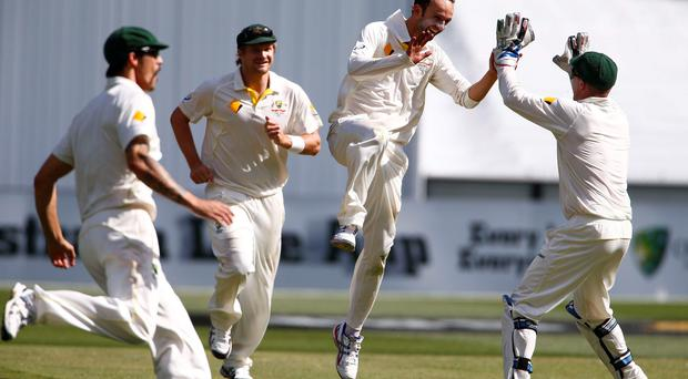 Australia's Nathan Lyon (2nd R) celebrates his 100th test wicket with team mates during the third day of the fourth Ashes cricket test against England at the Melbourne cricket ground