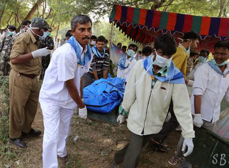 Hospital staff and volunteers carry a body of a passenger near the site of a train accident at Kothacheruvu, about 155km (96 miles) north of Bangalore, India