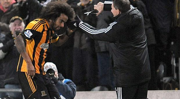 Hull City's Tom Huddlestone (left) celebrates scoring their fourth goal of the game with an impromptu hair cut during the Barclays Premier League match at the KC Stadium