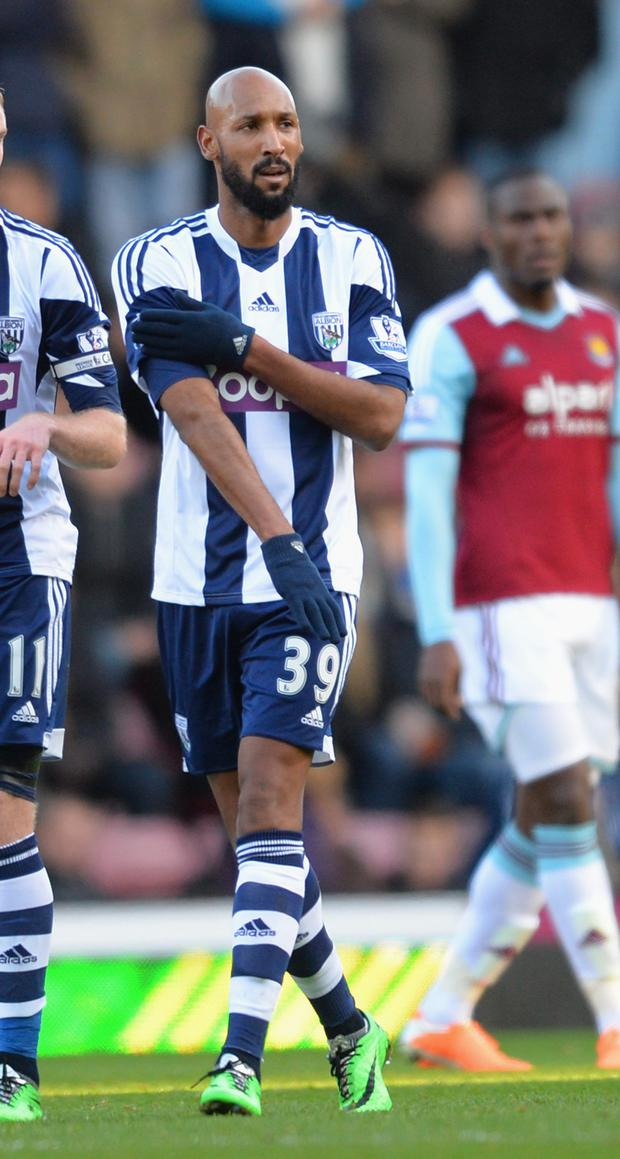Nicolas Anelka of West Brom touches his sleeve as he celebrates scoring their first goal during the Barclays Premier League match between West Ham United and West Bromwich Albion