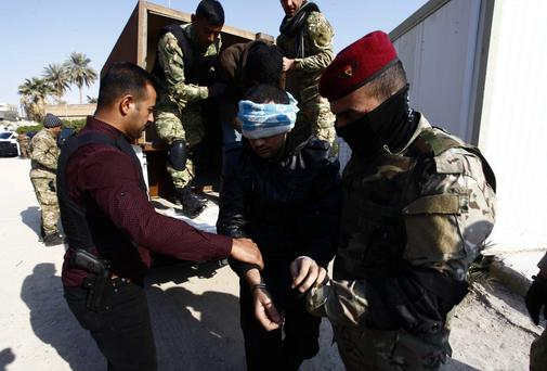 Iraqi security forces personnel arrest suspected militants during a raid and weapons search operation in north Babil province