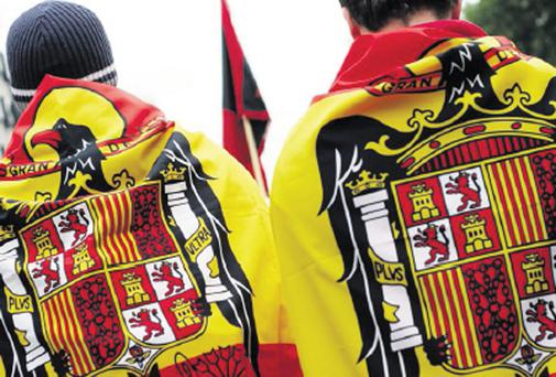 Right-wing demonstrators draped in Spanish flags take part in a march in Madrid