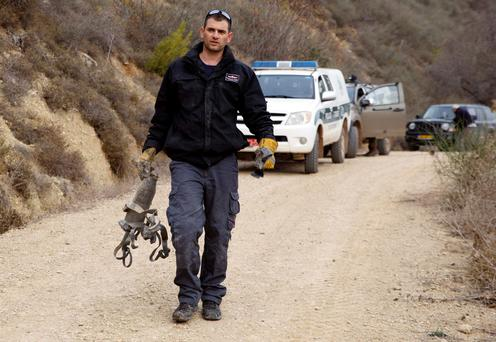 An Israeli police explosive expert carries the remains of a rocket after it landed near the northern town of Kiryat Shmona December 29, 2013