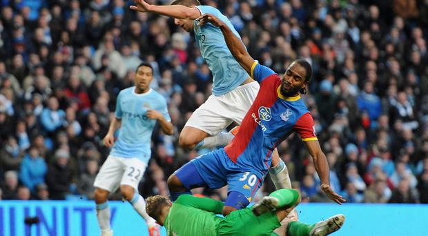 Joe Hart of Manchester City dives at the feet of Cameron Jerome of Crystal Palace