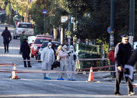 Police experts search for evidence following a gun attack, outside the German ambassador's residence in Chalandri suburb north of Athens