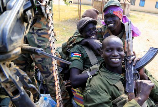 South Sudan army soldiers hold their weapons as they smile in Malakal town, 497km (308 miles) northeast of capital Juba.