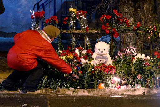 A women puts a flower outside a wreckage of a trolleybus in Volgograd, Russia, Tuesday, Dec. 31, 2013. Russian authorities ordered police to beef up security at train stations and other facilities across the country after a suicide bomber killed 14 people on a bus Monday in the southern city of Volgograd. It was the second deadly attack in two days on the city that lies just 400 miles (650 kilometers) from the site of the 2014 Winter Olympics. (AP Photo/Denis Tyrin)