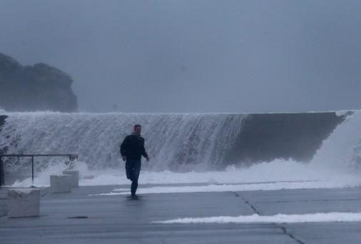 A man runs from waves crashing onto the East pier in Howth, Dublin. Photo: Brian Lawless/PA Wire