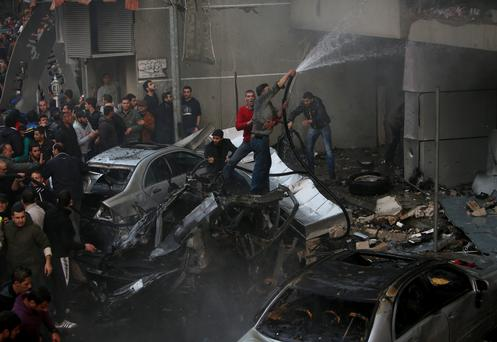 Lebanese citizens hose damaged shops as they stand on burned cars at the site of an explosion in a stronghold of the Shiite Hezbollah group at the southern suburb of Beirut. The explosion took place during rush hour in the Haret Hreik neighborhood, killing several people, setting cars ablaze and sending a column of black smoke above the Beirut skyline. Credit: AP Photo/Hussein Malla