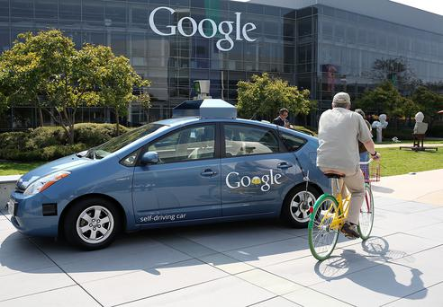 A bicyclist rides by a Google self-driving car at the Google headquarters. Apple is now developing a self-driving car